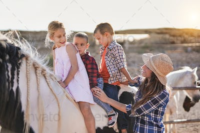 Kids riding a horse outdoor at ranch - Happy mother with children - Animal love
