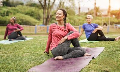 Multi generational women doing yoga exercise at park