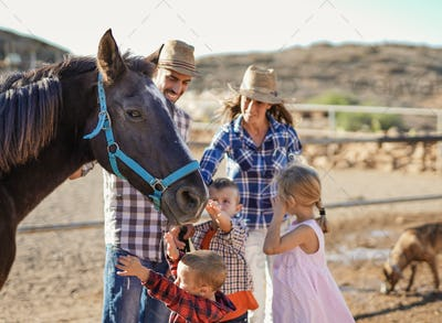 Happy family cuddle horse outdoor ar ranch - Human and animal love