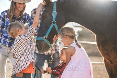 Cheerful family enjoy day outdoor at ranch while the children cuddle a horse - Human and animal love