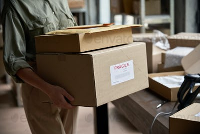 Female worker holding shipping order boxes in warehouse, closeup.