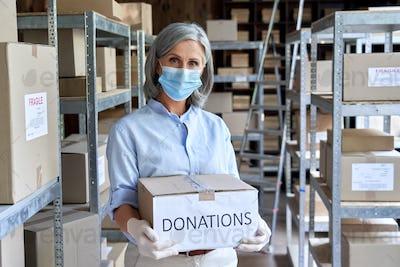 Mature female warehouse worker wearing mask holding donations box.