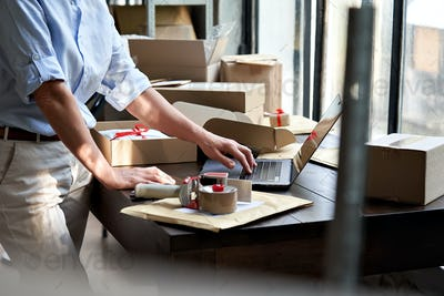 Female online business owner packing shipping ecommerce parcel using laptop.