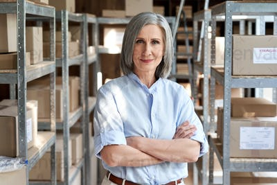 Confident older woman manager standing in delivery shipping warehouse, portrait.