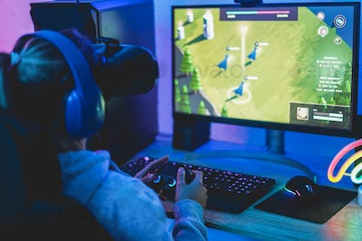 Girl gamer playing strategy game online using virtual reality headset - Focus on joypad controller