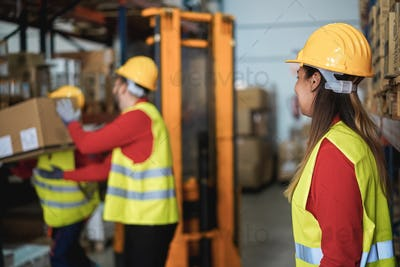 Industrial workers loading delivery boxes inside warehouse store - Focus on woman head