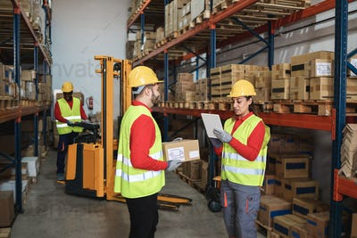 Multiracial workers talking inside warehouse store - Focus on woman face