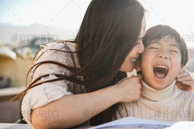 Happy asian young mother having tender moment with her child outdoors