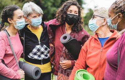 Multi generational women having fun before yoga class wearing safety masks