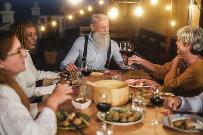 Senior multiracial friends cheering with wine and eating outdoors - Focus on center woman