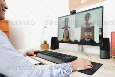 African woman having video call with her colleagues using computer app - Focus on right hand