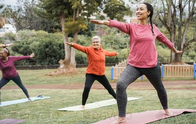 Multi generational people doing yoga class keeping at city park - Focus on right girl face