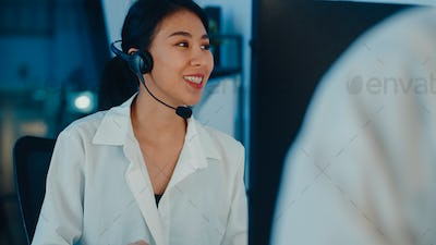Asia young call center team using computer and microphone headset working.