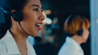 Asia young call center team using computer and microphone headset working in late night office.