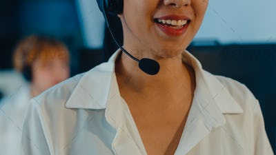 Closeup of Asia young call center team using computer and microphone headset working.