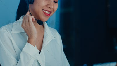 Asia young call center agent using computer and microphone headset.