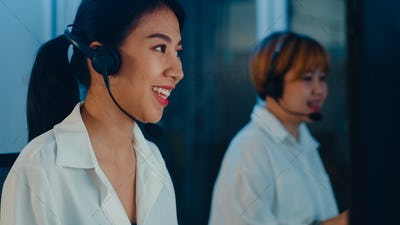 Millennial Asia young call center team using computer and microphone headset working.