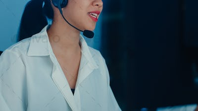 Millennial Asia young call center agent using computer and microphone headset working.