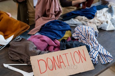 A heap of donation clothes on wooden table