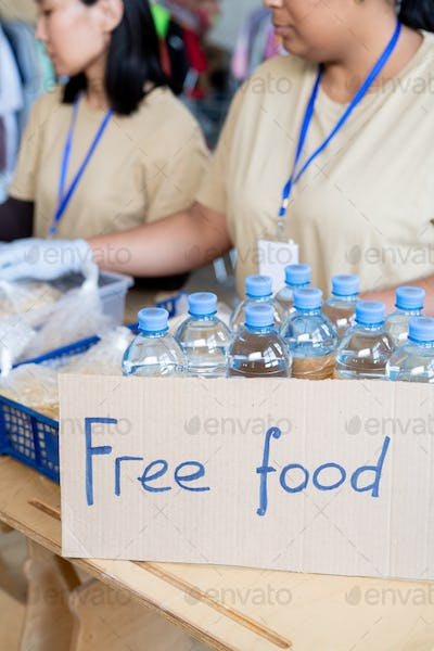 Female volunteers donating free food and plastic bottles with water