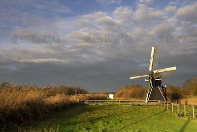 The Follega windmill under a heavy clouded sky