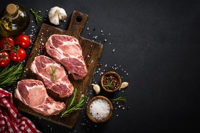 Pork meat at wooden board on black table