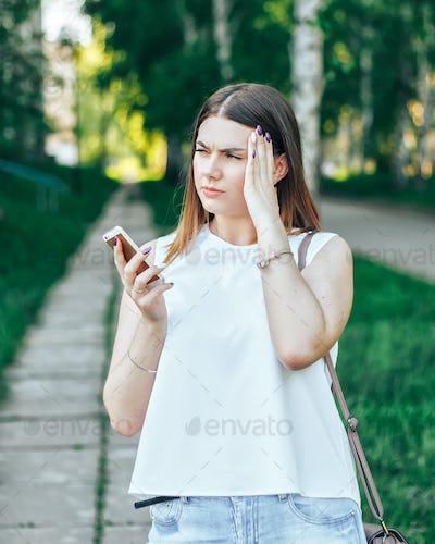 beautiful girl has headache, she holding smartphone in hands, she walking in park