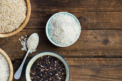 Different types of rice in wooden bowls such as basmati, brown a