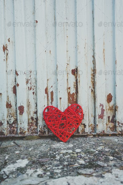 Grunge design of a red heart in an old wall