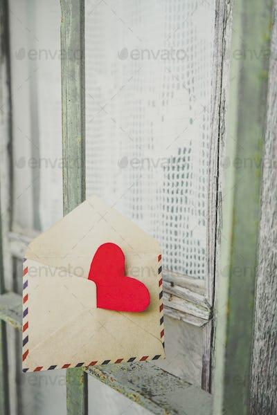 Red heart inside an old envelope