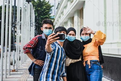 Group of friends wearing mask and selfie with phone