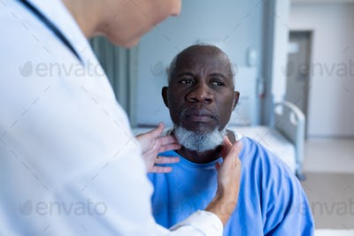 Caucasian female doctor palpating lymph nodes of african american male patient