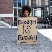 Portrait of mixed race woman holding placard
