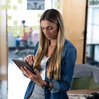 Caucasian businesswoman standing at desk in meeting room using digital tablet