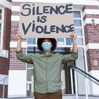 Portrait of mixed race man wearing a face mask holding placard