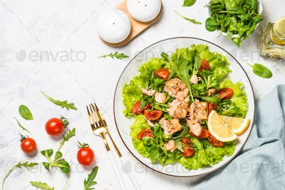 Green salad with baked fish at white table