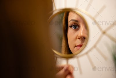 Young Woman Looking At Her Reflection In Beauty Clinic