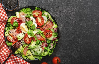 Fresh salad with salted salmon, avocado, egg, sesame seeds, olive oil, tomatoes