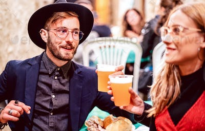 Young couple toasting beer glasses at street food festival