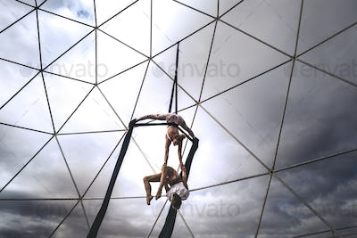 Couple team peole of acrobatice air dance traing together for perfect exhibition balanced