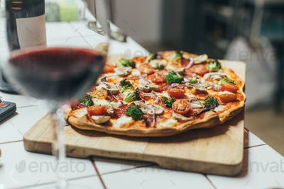Cook holds homemade pizza on wooden board
