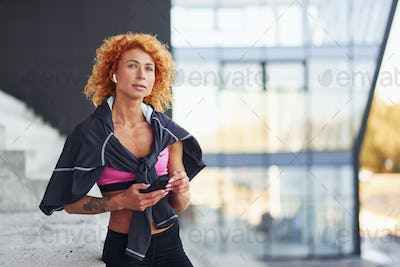 Young european redhead woman in sportive clothes standing on stairs outdoors with phone in hands