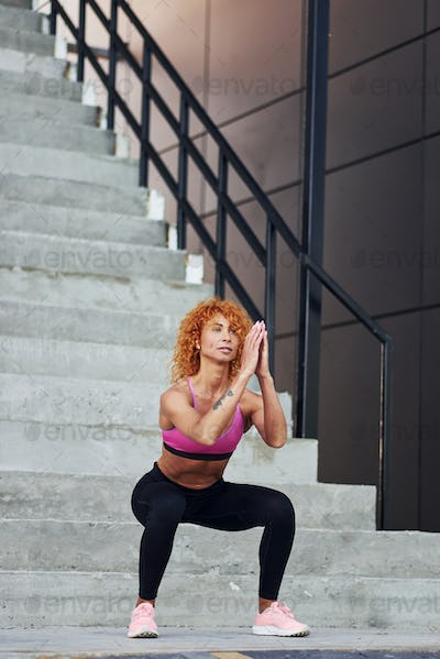 Young european redhead woman in sportive clothes doing squats outdoors