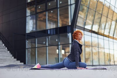 Young european redhead woman in sportive clothes doing fitness outdoors
