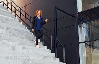 Young european redhead woman have walk on the stairs outdoors