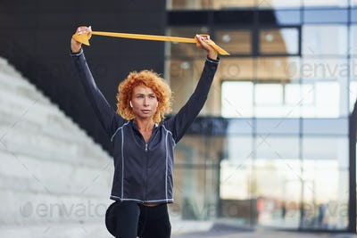 Young european redhead woman in sportive clothes doing exercises with rope outdoors