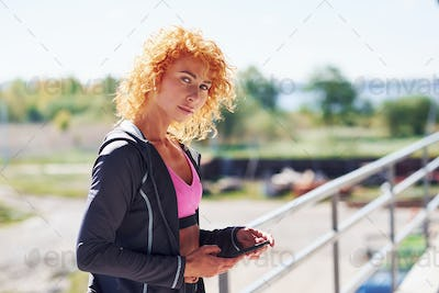Young european redhead woman in sportive clothes standing outdoors with phone in hands
