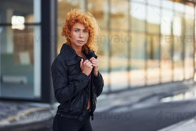Young european redhead woman in sportive clothes standing outdoors