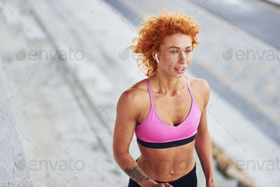 Young european redhead woman in sportive clothes running outdoors