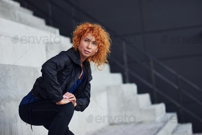 Young european redhead woman in sportive clothes doing exercises on stairs outdoors